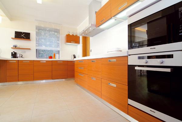 Atypický nábytok rovnako ako kuchynskú linku a interiérové dvere im vyhotovili z MDF s povrchom z prírodnej dyhy. Pracovná doska a stena za pracovnou plochou v kuchyni sú z corianu.