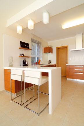 Hrany a čisté formy sa pripomínajú aj vo vysunutom bielom ramene malého barového stola s dvoma stoličkami.