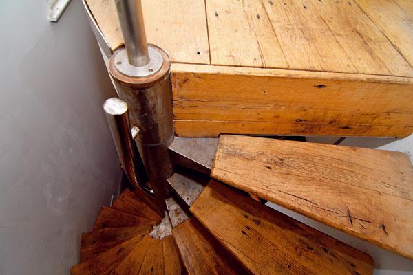 Vhodne umiestnená sedačka opticky rozšírila úzky priestor a drevená masívna podlaha i schodisko zas vyvážili Kennyho výber neutrálnych farieb a kovu.