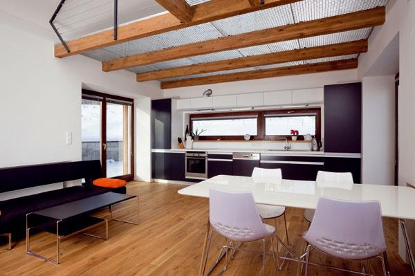 Moderné zariadenie chalupy, prírodné materiály na podlahe aefekt spojenia obnažených stropných trámov skovovým roštom vniesli do interiéru netradičný súlad.