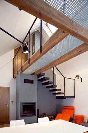 Do podkrovia sa popri kozube dvíhajú oceľové schody kmiestnosti vpodstreší, ktorú možno využiť ako druhú spálňu alebo hosťovskú.