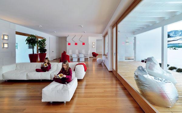 Pred jedálenským stolom predstupuje múr schodiska, ktoré vedie do priestranného fitnes vsuteréne.