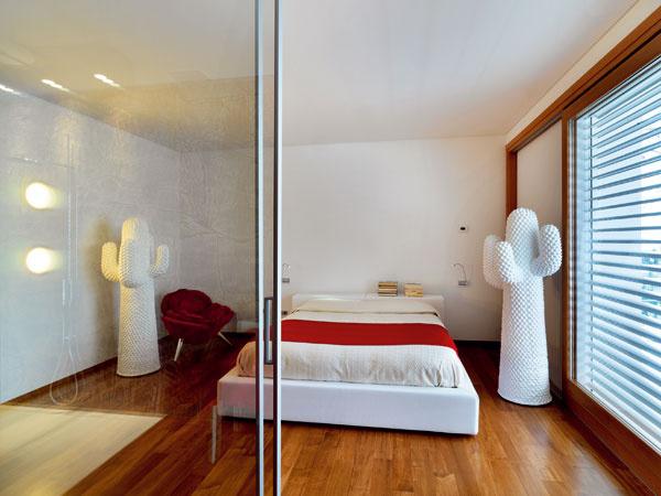 Veľká spálňa skúpeľňou oddelenou odsúvacími dverami, zktorej na snímkach vidieť len prednú časť sumývadlovou súpravou od firmy Kos alakovaným plastovým kreslom Panton Clasic, aké sú aj vjedálni.