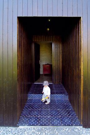 Aby ani vstup do domu nevyčnieval z línií stanovených pravidlami kocky, architekt nevyužil klasické riešenie v podobe predsadeného závetria či markízy, aj tak je však prichádzajúci šikovne chránený pred nepriazňou počasia.