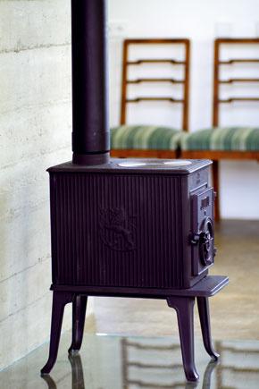 Pôvabná piecka pred betónovou akumulačnou stenou ladí a dotvára atmosféru, aj keď sa v nej práve nekúri.