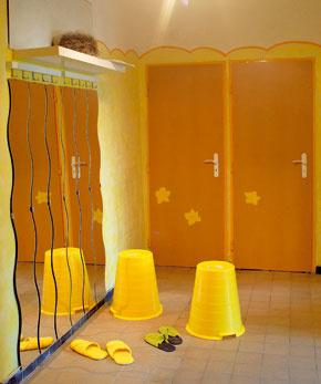 """Do rozľahlej chodby mohli bez ujmy na priestore umiestniť aj pomerne veľkú skriňu. Ako väčšina chodieb, ani táto nemá okná, takže hrozilo, že bude trochu ponurá. Vyriešila to opäť farebnosť, tentoraz kombinácia bielej a žltej, a zasklené dvere na obývacej izbe aj spálni. Dvere na kuchyni odstránili a na dverách do WC a kúpeľne """"narástlo"""" zopár žltých kvetov."""