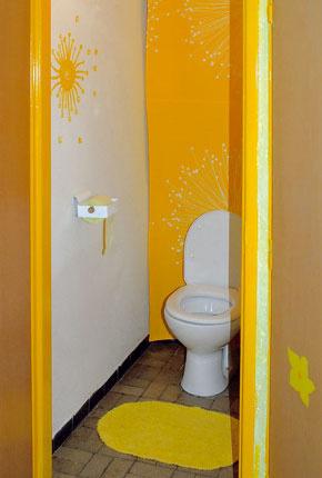 Aj v záchode vládnu radostné farby – biela a žltá – a steny zdobia motívy kvetov namaľované podľa závesu, ktorý zakrýva police s čistiacimi prostriedkami.