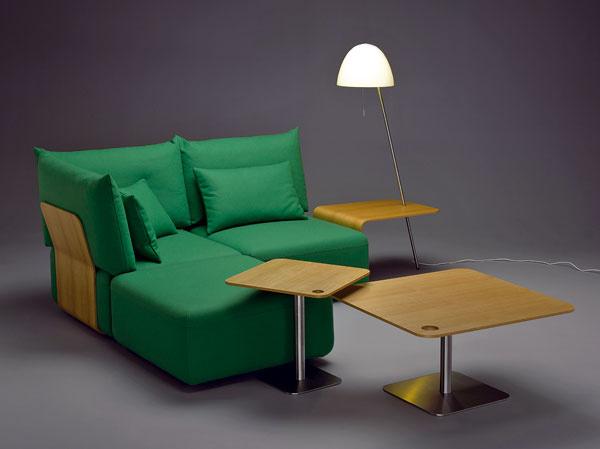 Rohové sedenie Flex od firmy mminterier, doplnené lampou apríručnými stolíkmi. Kostra zdreva, polyuretánová výplň sedenia, poťah zlátky alebo kože.  Lampa  cena 1 015 €. Stolík srozmermi 50 × 50 cm. Predáva Drella, Atrium.