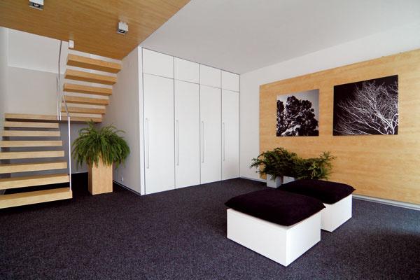 Za radom bielych skriniek vedľa schodiska majú domáci komoru.