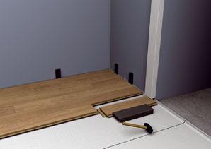 Úlohou podložky je odseparovať plávajúcu vrstvu podlahy od podkladu, tlmiť krokový hluk a vyrovnať drobné nerovnosti. Zasúvaním vymedzovacích kolíkov či blokov pred lamely sa postaráte o vynechanie a dodržanie štrbiny, teda dilatačnej medzery medzi stenou a podlahou v šírke 1 až 1,5 cm. Quick step_instalacia