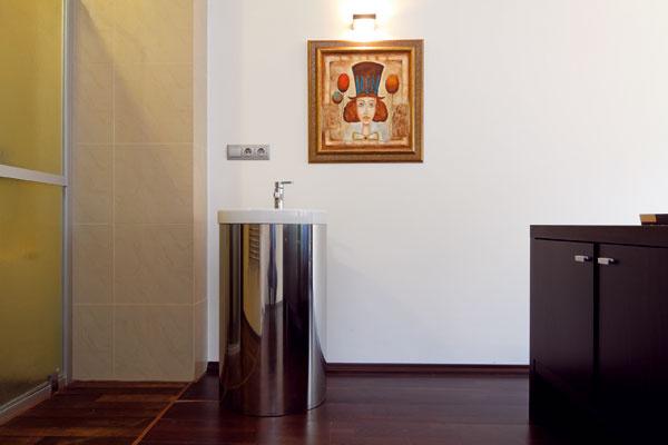 Teplé farby obrazu od výtvarníčky Diany Letkovičovej-Vidovej v zlatom ráme sú v peknom kontraste s kovovým podnožím solitéru s umývadlom.