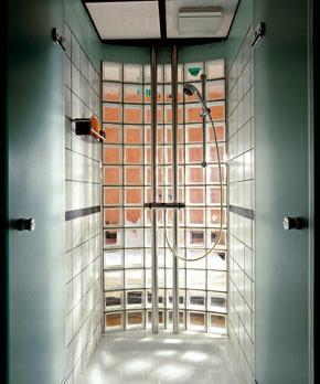 Interiér kúpeľne sa celkom odovzdal rastrovaniu. Začalo sa to obkladom na stenách, pokračovalo oblúkom zo sklobetónových tvárnic a prikrylo sa podhľadom v znamení štvorcov. Cez sklenenú priečku presvitajú obrysy lôžka. (Foto: Reiner Blunck)