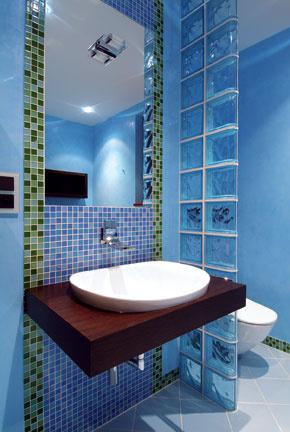 Sklobetónovú polopriečku nechali voľne vysunutú do priestoru. Padá od stropu k podlahe ako vodný stĺp, decentne oddeľuje, netrčí… Tvar sklenej tvarovky neupravíte, v ponuke sú však i okrajové či rohové prvky v rôznych farebných odtieňoch. (Foto: Sklobetón)
