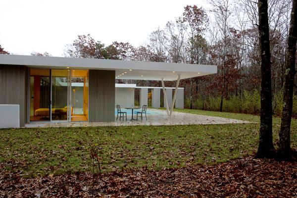Terasa s hliníkovým záhradným nábytkom a letnou kuchyňou susedí s priehľadnou spálňou domácich. Presah plochej strechy vytvára markízu, ktorá chráni terasu pred dažďom aj prudkým slnkom.