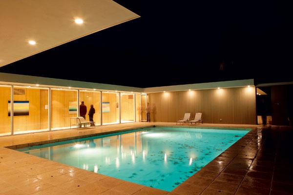 Bazén lemovaný dlažbou zo svetlého travertínu a neďaleký dubový les sú kľúčovými prvkami oddychovej zóny so spálňami.