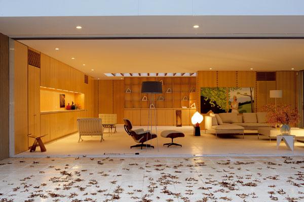 Veľkoryso riešený obytný priestor plynule prechádza do travertínovej terasy, ktorá ho rozširuje smerom k lesu. Vďaka zasúvacím skleneným dverám sa môže interiér v celej svojej šírke plynulo prepojiť s exteriérom.