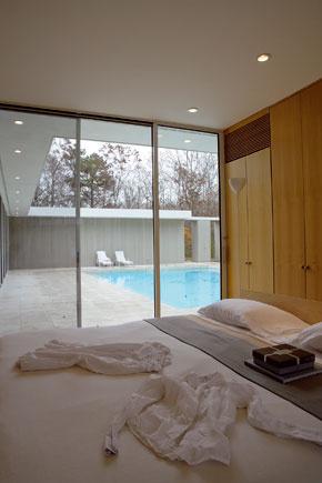 Na jednej strane priehľadnej spálne domácich rámuje sklenená stena pohľad na pokojné zátišie s bazénom, na opačnej sa otvára lesu.