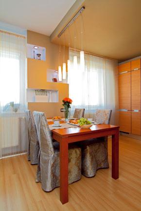 Pôvodné svietidlá museli trochu zmeniť miesto, aby boli presne nad jedálenským stolom. Zároveň zdôrazňujú naznačenú hranicu medzi obývačkou akuchyňou. Bodové osvetlenie sa zabudovalo aj do zníženého stropu ado ník – aj vďaka odlišnému svetlu vytvorila kuchyňa kompaktnejší celok.