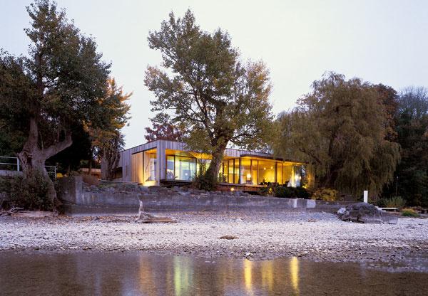 Na snímke z úzkeho kamenistého jazyka vybiehajúceho do vody dobre vidieť, ako architekt strieškou na pravej časti priečelia narušil jednoduchú lineárnosť domu.