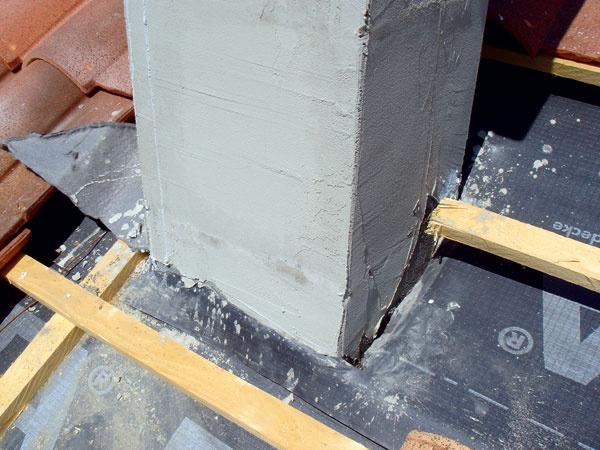 Nekvalitné napojenie hydroizolačnej fólie na komín. Ak by sa dostala voda pod strešnú krytinu napríklad v dôsledku náporového dažďa, jej prieniku by takto vyriešená fólia, ktorá je na to určená, nezabránila. (foto: Villa Testa)