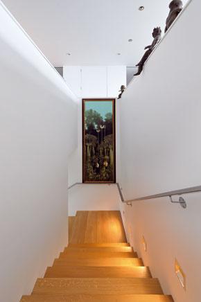 Na schodisko sa vstupuje priamo oproti vchodovým dverám. Jeho zalomená rampa stúpa na prízemí medzi múrmi úžitkových priestorov.