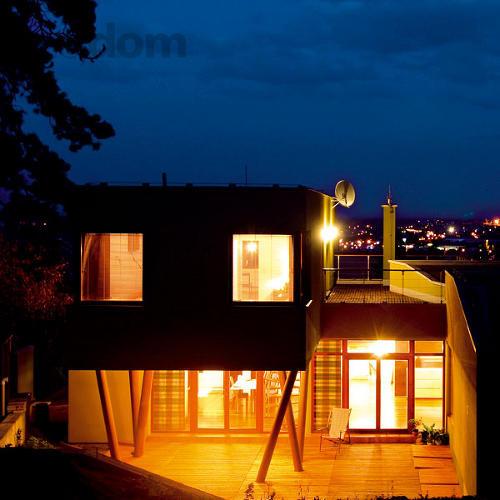 Drevené plošiny, vysunuté kubusy – jeden z nich, podobne ako vysunutá hlava domu do ulice, sa opiera o les stĺpov, ktoré pripomínajú neďalekú borinu aj pri večernom osvetlení.
