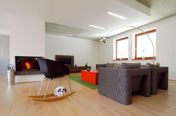 Znížené biele časti stropu a o 40 centimetrov vyššie odhalená podstata betónovej šedi pridali priestoru prízemia na plasticite. Tá svojou výtvarnosťou korunuje inak jednoduchú otvorenú dispozíciu obývačky, jedálne a kuchyne.