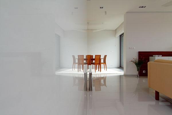 Drevený nábytok pôsobí na bielom lesku podlahy celkom ľahúčko. Stena vľavo vznikla pri prestavbe. Za ňou sa dvíha schodisko na poschodie so spálňami, pracovňou akúpeľňami.