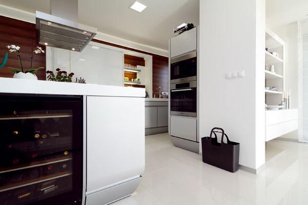 """Kuchynské biele krídlo zakončuje zabudovaná vinotéka. Stena, ktorá tvorí """"závetrie"""" pre policu sporcelánom, je jedným znosných prvkov konštrukcie domu."""