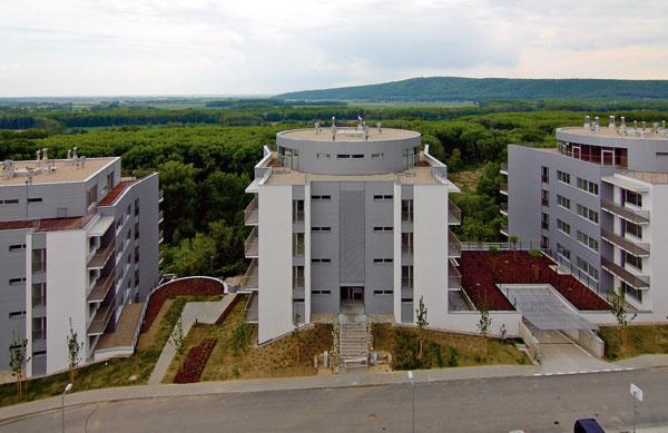 Nad Devínskou cestou vBratislave na Dlhých dieloch sa sedem terasových domov Condominia Renaissance obracia zasklenými stenami kjuhu.