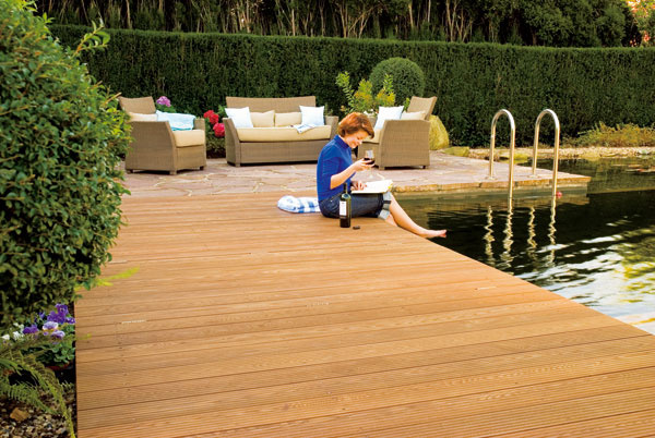 Dojem zvašej súkromnej vodnej plochy aj pôžitok zkúpania môže zvýšiť vhodne zvolené miesto aj úprava okolia – od hlavného vstupu do domu aj od ostatnej záhrady ju môže opticky oddeliť napríklad tvarovaný živý plot. terasa zjaseňového dreva ošetreného olejom; foto: Osmo Holz und Color