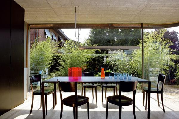 Jedálenská časť so stolom od Kaspara Wetliho, stoličky od firmy Horgen-Glarus, nad tým všetkým stropné svietidlo Updown od firmy Belux.