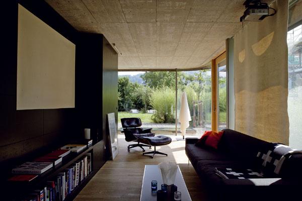 Jeden z nosných betónových blokov v centre obytného priestoru tvorí stenu kuchyne, zároveň je oporou pre schodisko a z opačnej strany knižnicou. Pohovka od firmy mdf Italia a k nej relaxačné kreslo s podnožkou od Ray a Charlesa Eamesovcov.