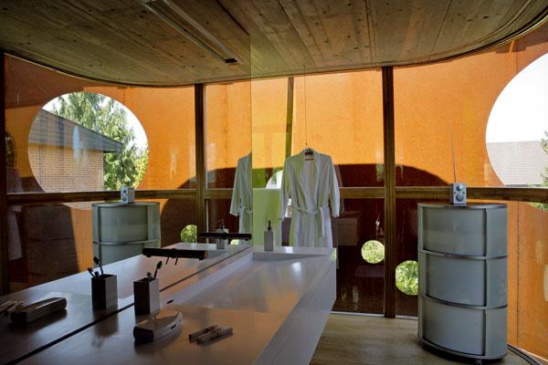Druhá časť kúpeľne s umývadlom z corianu a nábytkom na kolieskach od firmy Wogg. Veľké zrkadlo odráža oceľový pás vinúci sa okolo fasády a spolu s medzerou medzi sklom a oceľou opticky rozširuje priestor miestnosti.