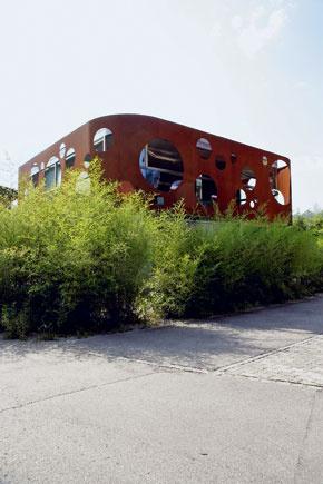 Neobyčajný dom v obyčajnej štvrti – z diaľky vidieť iba oceľovú masku, ktorá akoby sa vznášala nad bambusovým plotom.