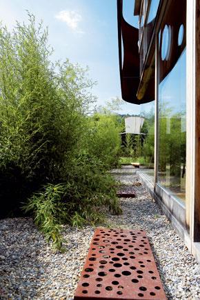 Charakteristický prvok domu – oceľový pás – je upevnený pred sklenenou fasádou asi vo vzdialenosti dĺžky ľudského ramena. Perforované kryty svetlíkov ladia s oceľovou maskou.