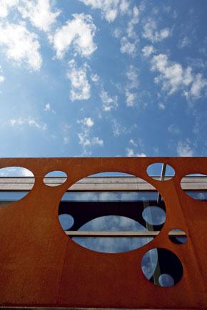 Okrúhle otvory rozličných veľkostí sú umiestnené na oceľovom páse akoby náhodne, pripomínajúc oblaky alebo hviezdy na nebi.