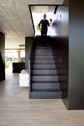 Od vstupných dverí môžete zamieriť vľavo k šatníku alebo mierne doprava ku schodisku na poschodie. Podlaha je z dubových dosiek bez povrchovej úpravy, betónový strop nesie stopy po drevenom debnení – všetky materiály použité v dome sú jednoduché a prirodzené.