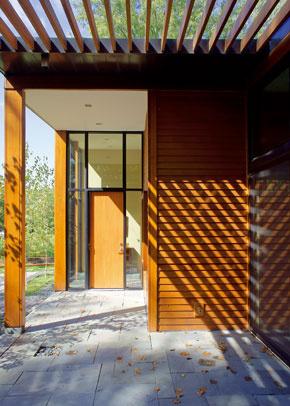 Hlavný vchod je zakrytý presahom strechy. Vstupuje sa ním do členitého denného priestoru, ktorého jednotlivé zóny sú oddelené iba nábytkom.
