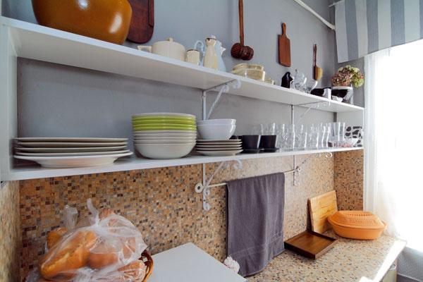 Kuchynské okno takmer na celú šírku steny dostatočne osvetľuje pracovné dosky. Za umne zavesenou utierkou majú skrytú elektrickú zásuvku.