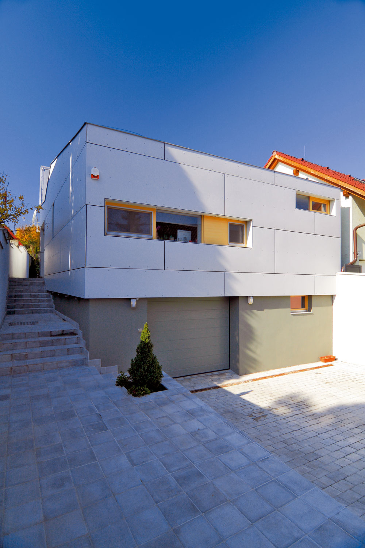 Tmavá sivá omietka, nenápadné prízemie, garážové dvere. Podľa architektonického návrhu priestor sgarážou atechnickou miestnosťou polozapustili do svahu. Na nenápadnom podnoží lepšie vynikne elegancia obdĺžnikového priečelia obytnej časti domu. Pravidelný cementovotrieskový obklad tvorí odvetranú fasádu.