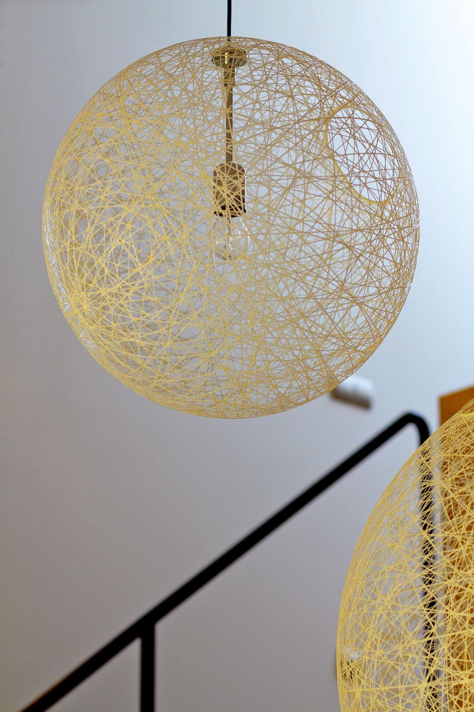 Ľahká štruktúra stropných svietidiel, ktoré sa vrôznej výške vznášajú pod šikminou strechy.