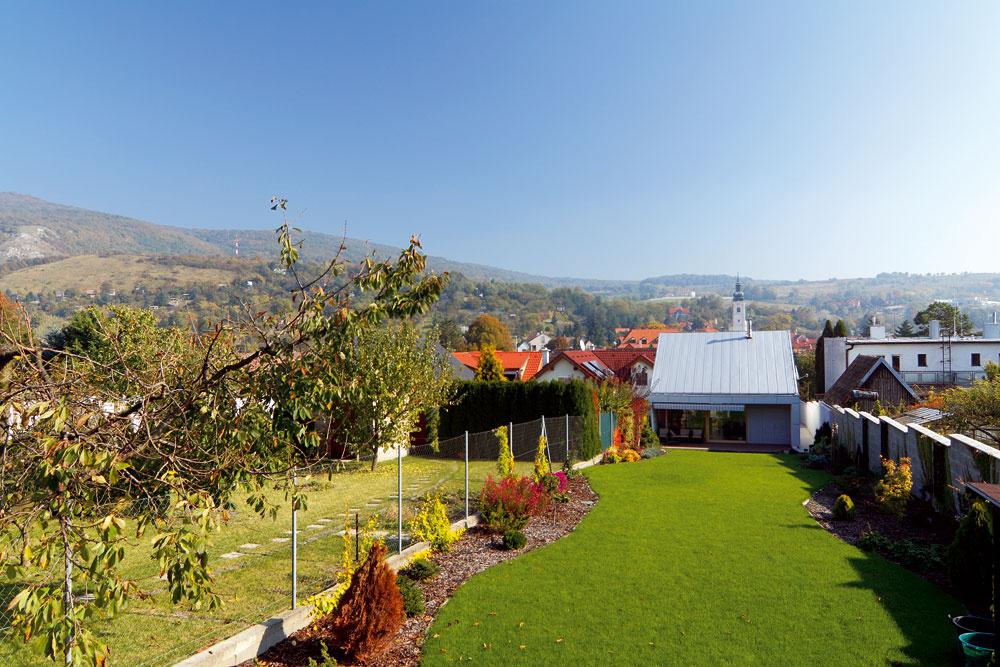 Sivý dom DEV opláštili prevetrávanou fasádou zcementotrieskových obkladových platní. Spoločenská časť domu sa otvára cez drevenú terasu do zeleného pruhu záhrady za domom.