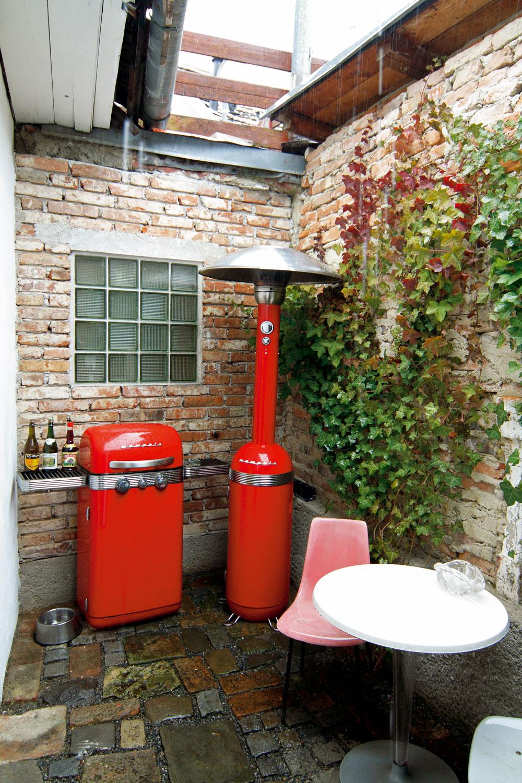 Vdvorčeku za galériou sa pod tehlovou stenou červená retro zátišie sgrilom. Okrúhlemu stolíku asistujú plastové stoličky zo 60. rokov.