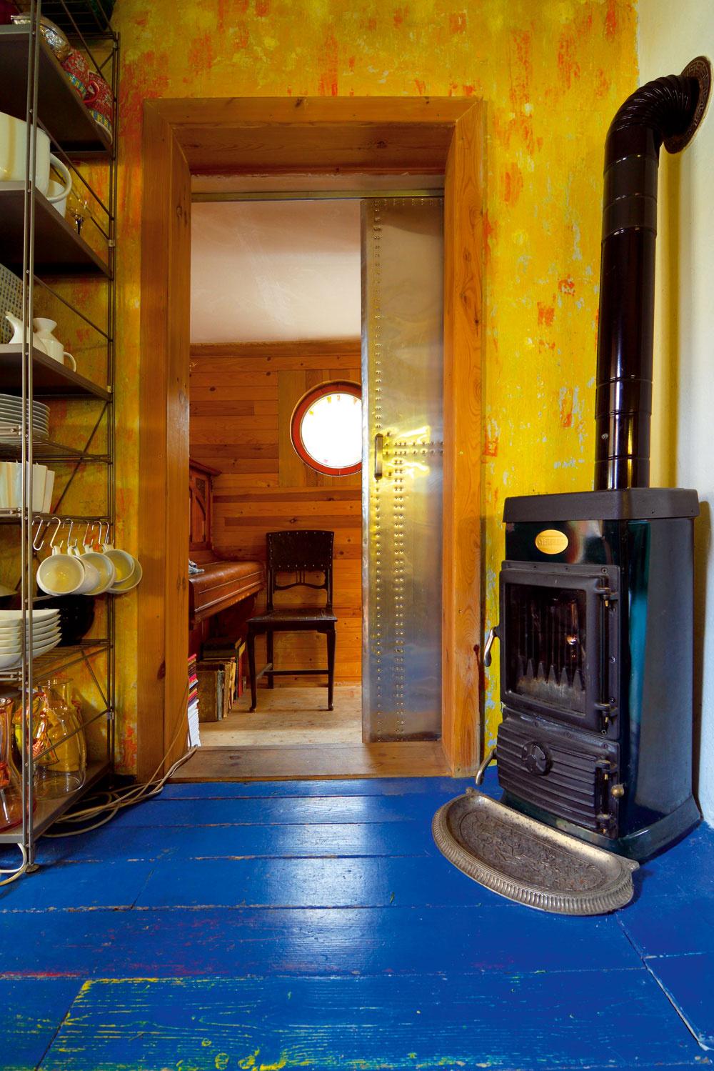 Vpriechodnej kuchyni udivuje priehľadná chladnička asympatický chaos. Jedny zposuvných dverí, ktoré vdome nahradili zväčša socíkové strašiaky. Tieto vedú do prístavku, ktorý navrhol avybudoval Peter ako nový vstup do ich prvého domu.