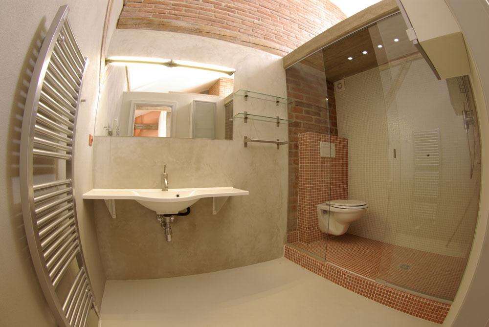 Vkúpeľňovej mozaike sa akoby pripomína farebnosť aštruktúra povrchu tehlového muriva. Toaletu distingvovane oddelili od ostatnej kúpeľne sklenenou priečkou aprekryli betónovým stropom.