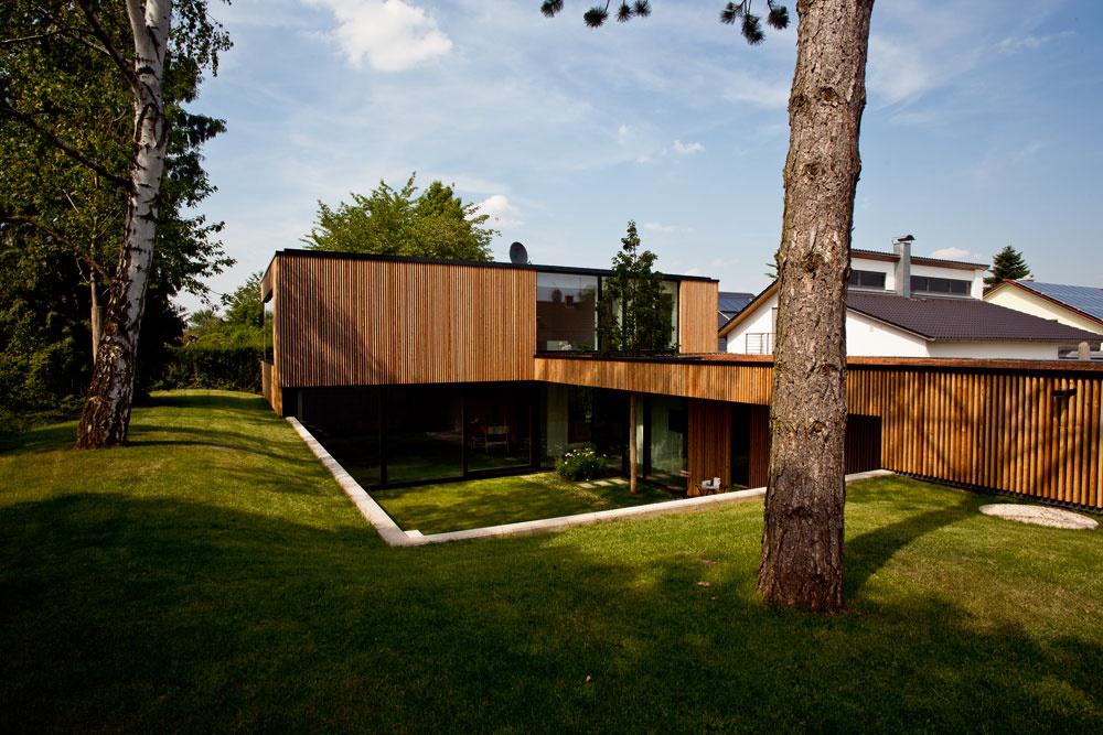 Architektka, ktorá tu býva spolu smanželom adieťaťom, vyriešila problémy spojené so zložitým pozemkom zahĺbením domu pod úroveň terénu aintrovertnou dispozíciou, otvorenou do chráneného átria. Zo severu avýchodu obkolesuje átrium drevom obložený dom, zo západu ajuhu (smerom kulici) vysoké stromy, betónový oporný múr azvyšok svahu, zktorého vznikol akýsi zemný val.