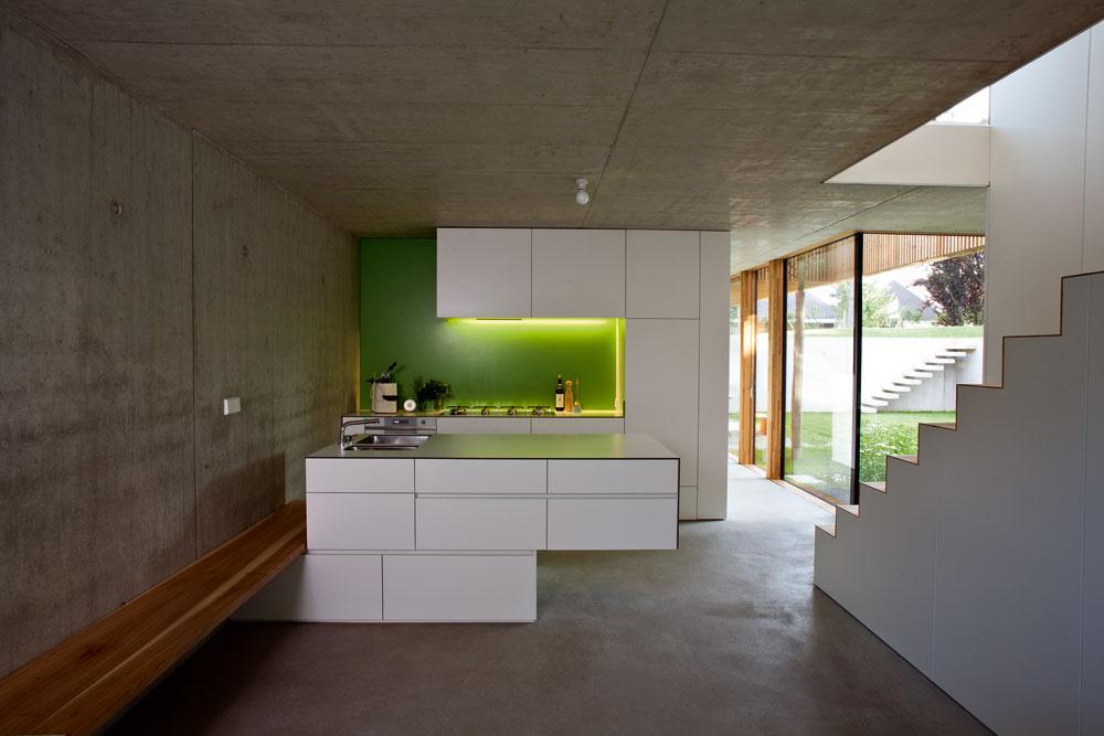 Zopačnej strany je biely kubus kuchynskou linkou. Vďaka vstavanému nábytku sa obytné priestory vyčistili apôsobia voľne aveľkoryso, farebná kombinácia bielej, sviežej zelenej adreva, typická pre celý dom, vnáša do interiéru optimistickú atmosféru.