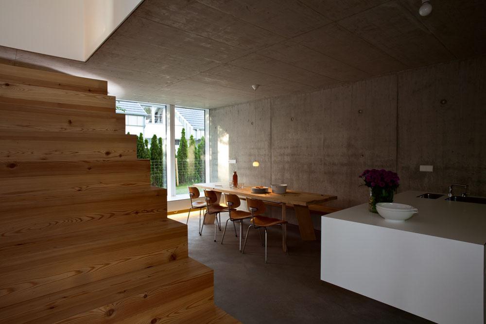 Aby dom pôsobil čo najpriestrannejšie, nie sú vdennom priestore žiadne priečky. Otvorená kuchyňa je spojená sjedálňou aod obývačky ju oddeľuje iba biely nábytkový kubus – tentoraz skriňovo-schodová kombinácia.