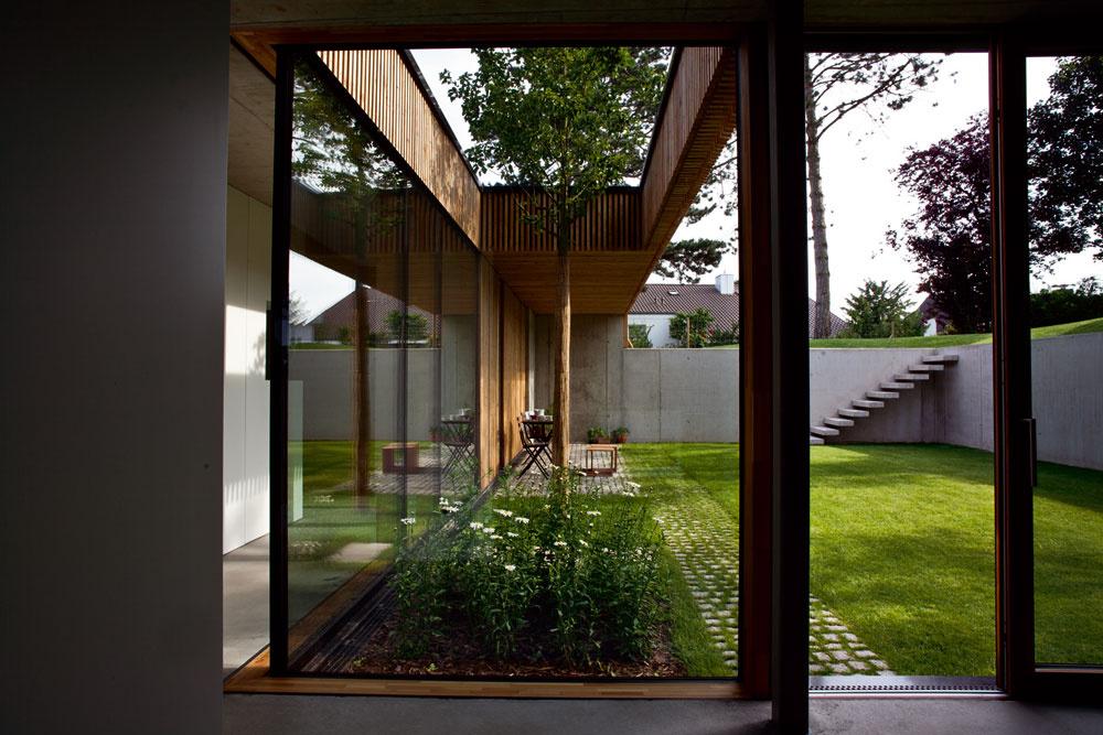 Prechod medzi interiérom aexteriérom je tu úplne plynulý: zprízemia domu sa cez posuvné zasklené steny otvárajú mnohé pohľady na múrmi obklopené átrium, aj viaceré možnosti vyjsť von. (Pohľad zobývačky smerom na juh.)